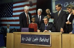 Visiting Hamilton High School in Hamilton, Ohio, Jan. 8, 2002, President George W. Bush signs into law the No Child Left Behind Act. On hand for the signing are Democratic Rep. George Miller of California (far left), Democratic U.S. Sen. Edward Kennedy of Massachusetts (center, left), Secretary of Education Rod Paige (center, behind President Bush), Republican Rep. John Boehner of Ohio, and Republican Sen. Judd Gregg of New Hampshire (not pictured). White House photo by Paul Morse.  Source: http://www.whitehouse.gov/news/releases/2002/01/images/20020108-1_20020108-1-515h.html
